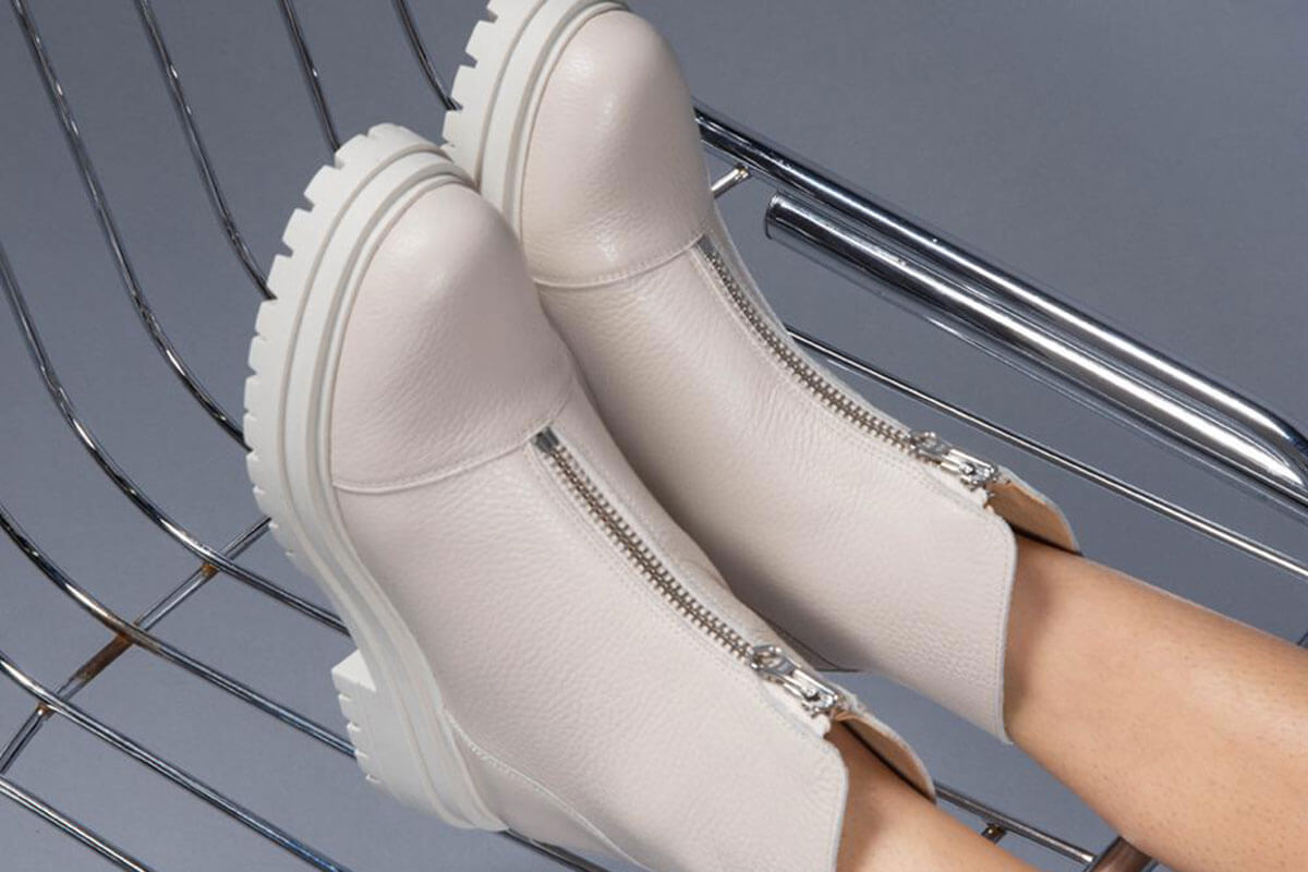 A pair of beige and white intervalle zip boots
