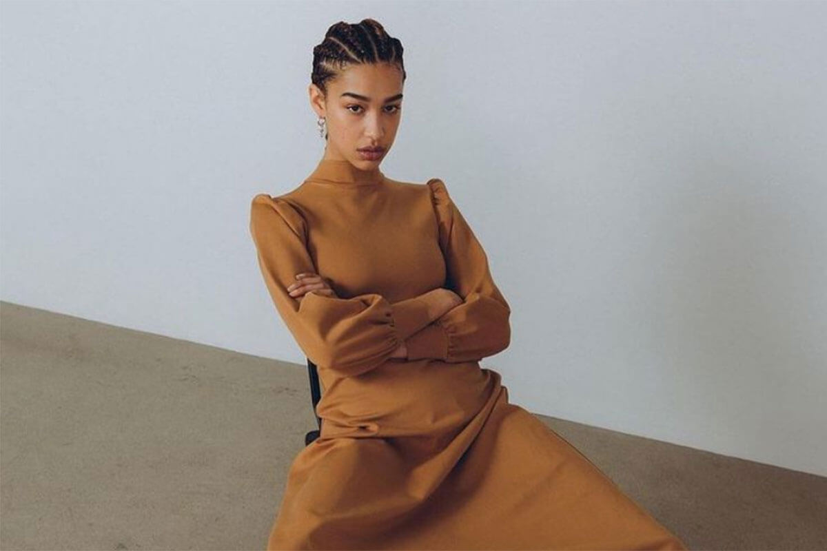 Ethical Canadian fashion brands deserve a look, and a seated woman displays a golden-bronze dress with high neck and long sleeves by Eliza Faulkner
