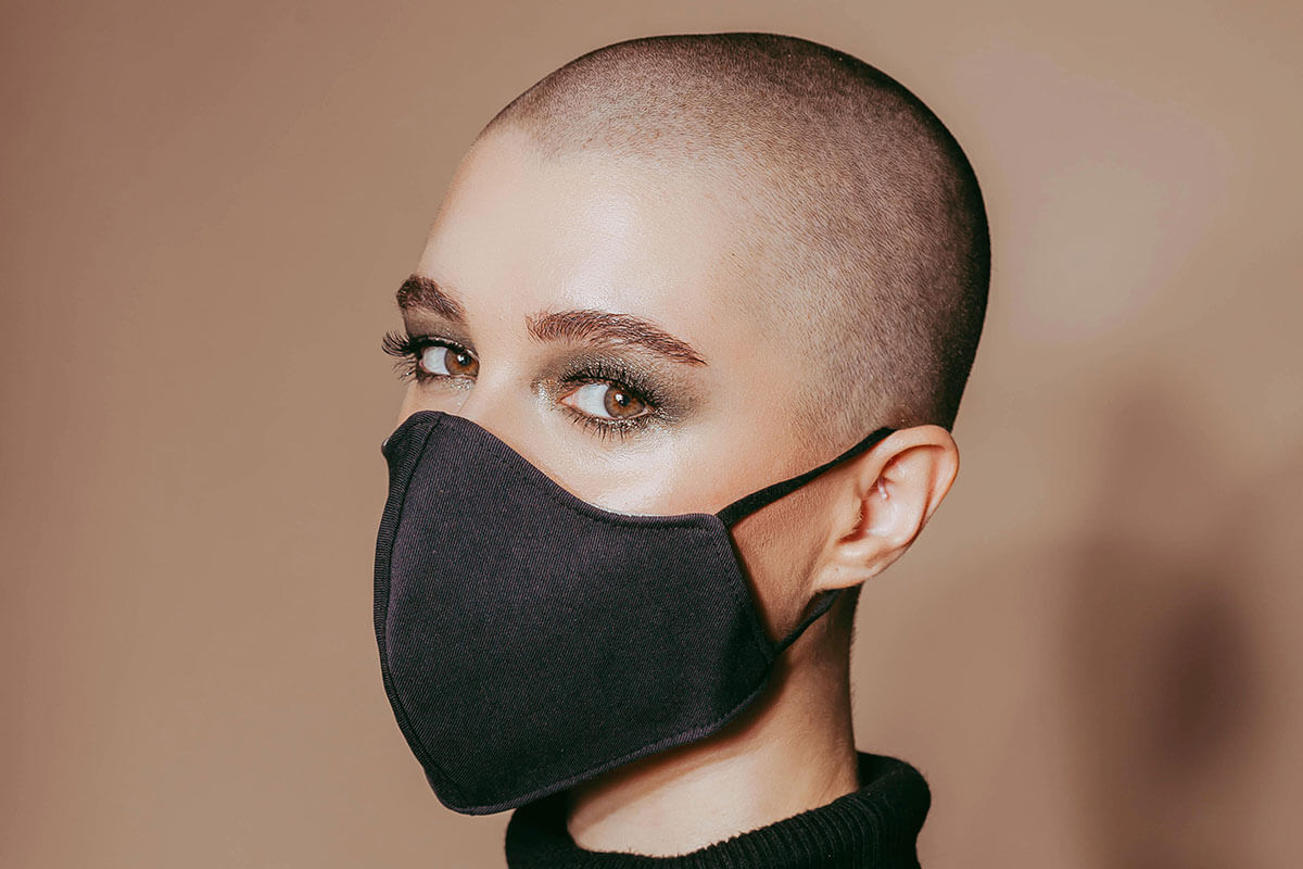 Woman with shaved head wearing a mask and minimal makeup