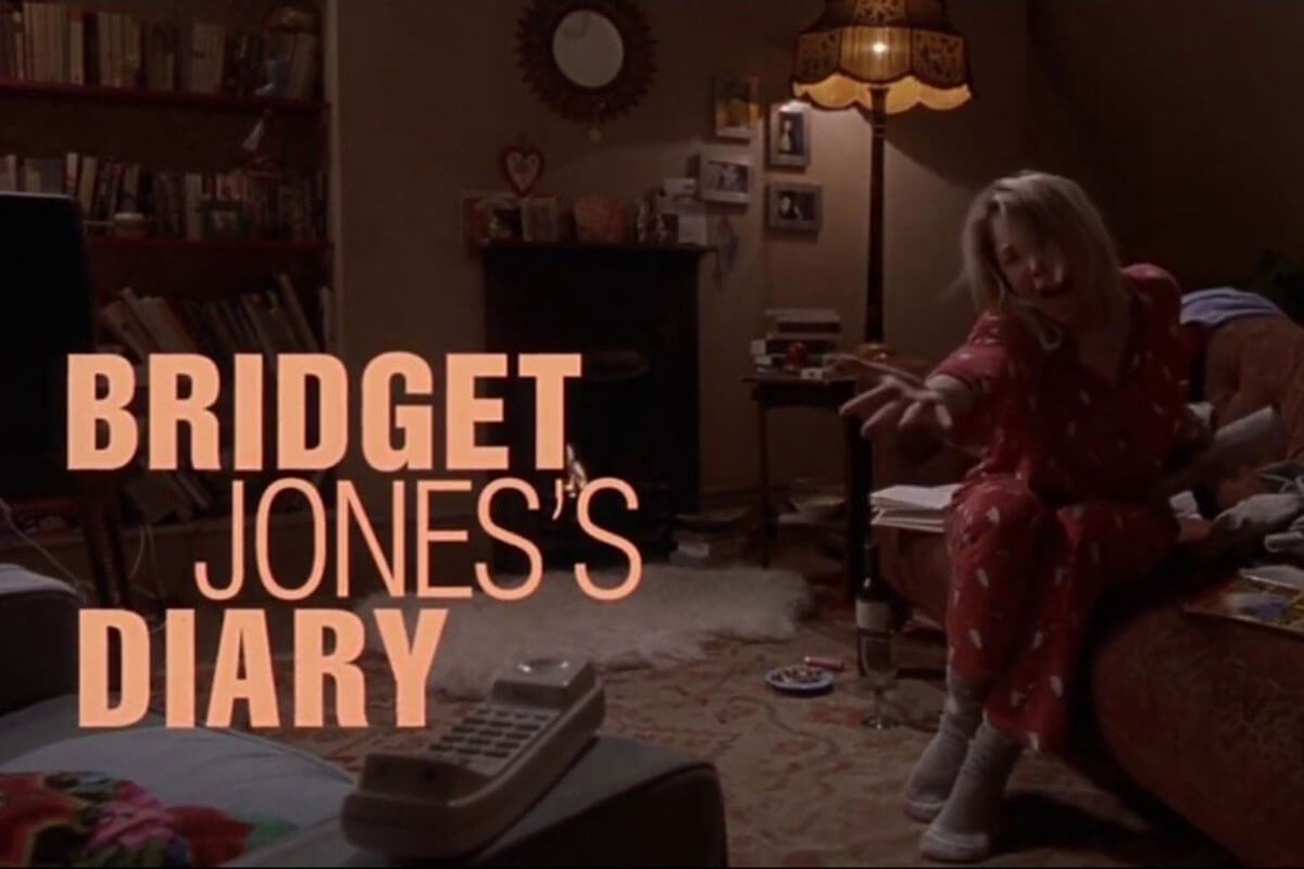 An upset Bridget Jones sitting on the couch in pajamas, one of Toast's curated must-watch TV & movie classics