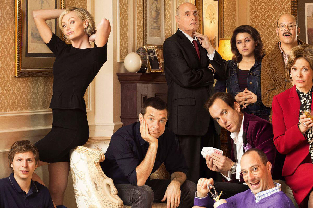 A group photo of the cast from Arrested Development, one of Toast's curated must-watch TV & movie classics