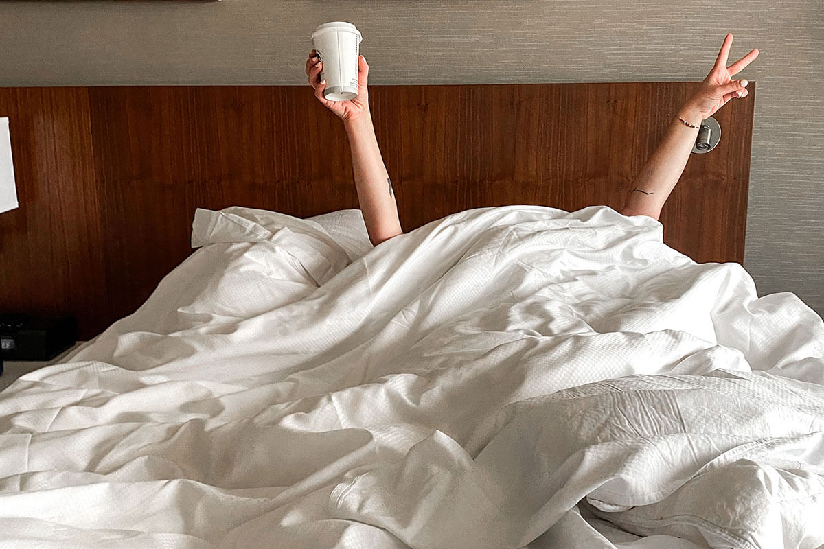 A girl under the bedcovers, celebrating with a takeout coffee