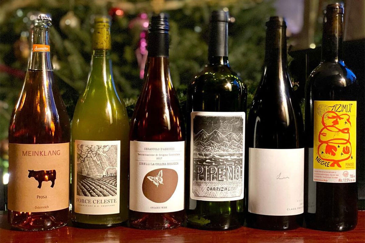 A row of six red and white wine bottles, all sustainably-farmed natural wines