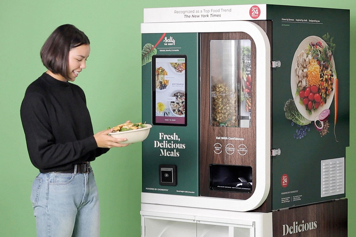 A girl standing beside a Chowbotics' Sally 2.0 machine with her freshly made salad