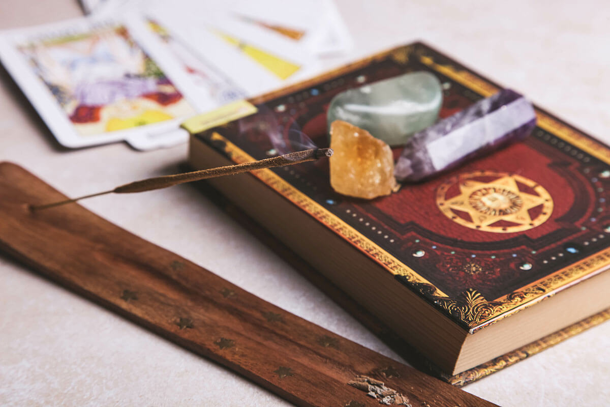 Toast wellness trend forecasts for 2021 include the rise of modern mystics, and this image shows crystals, incense, tarot cards and a book.
