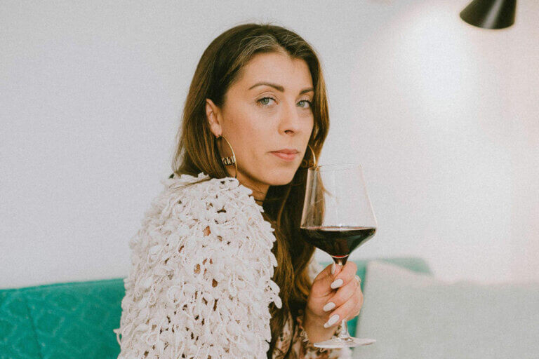 Samantha Rae from Metro Liquor Stores drinking a glass of red, one of the top wines under $25