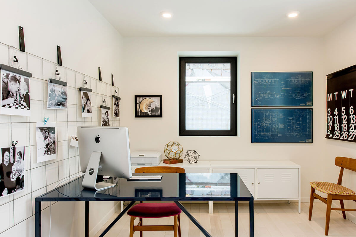 Home office with black table, accessories and white walls, part of 2021 home renovation trends