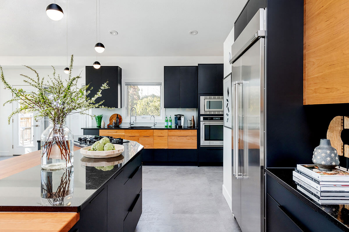 black, brown & stainless steel kitchen with grey flooring