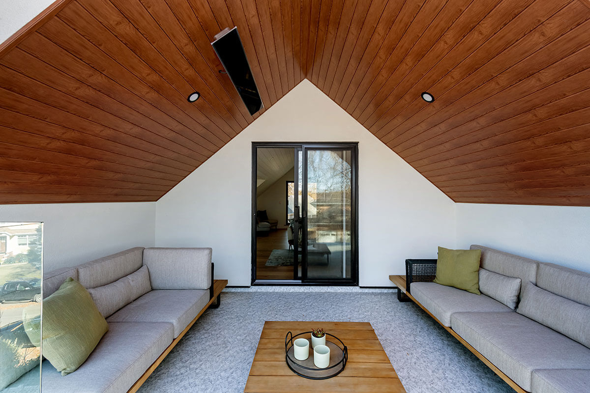 An outdoor living space attached to a house with wood ceiling, couches and ceiling heater