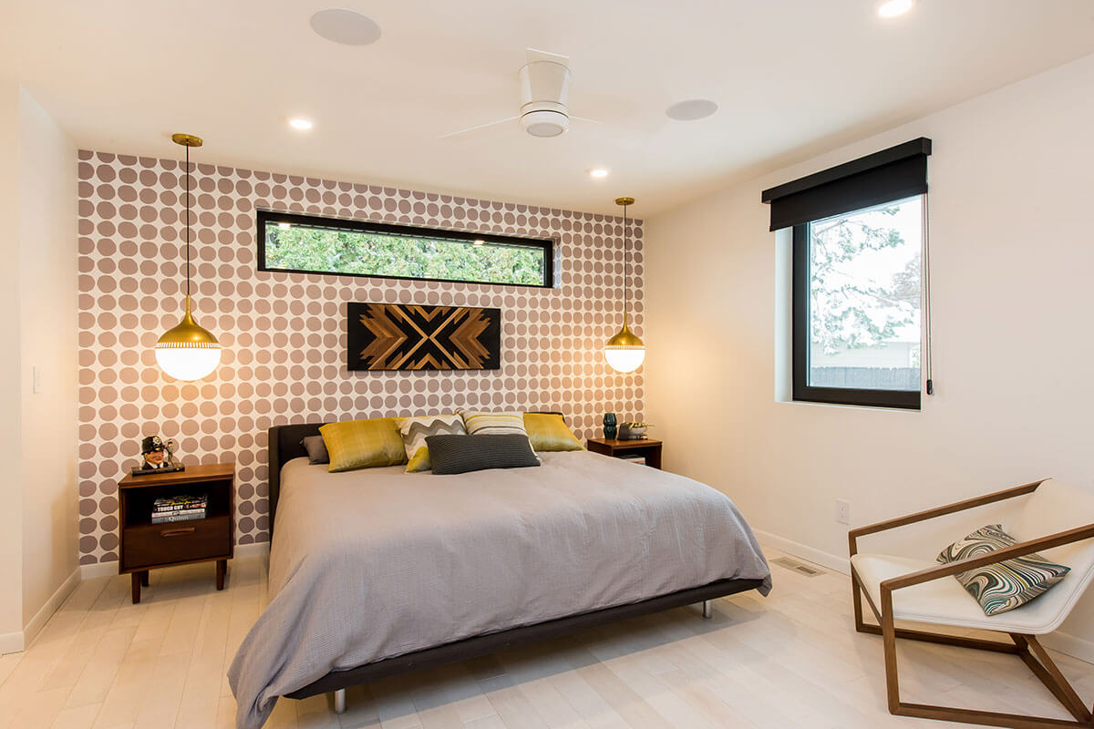 A bedroom with a feature wall of gold & white wallpaper, one of our 2021 home renovation trends