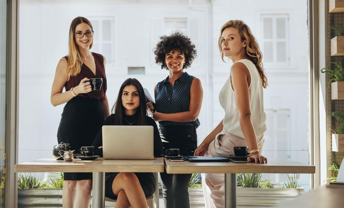 four businesswomen standing and sitting at a desk