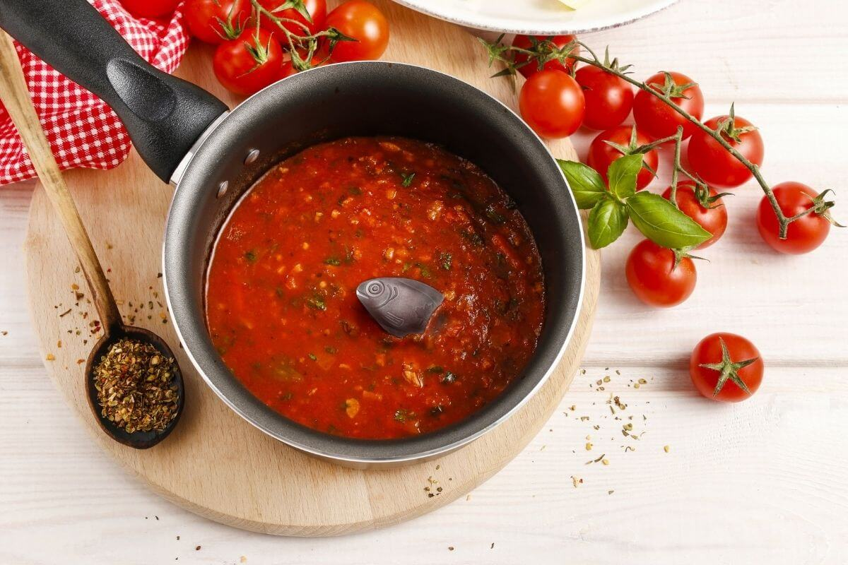 a pot of tomato soup with a small iron lucky fish laying in the midde to boost your iron intake