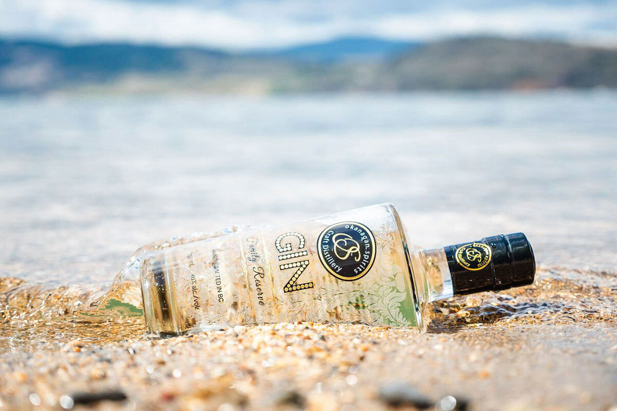 A bottle of Okanagan Spirits Craft Distillery Family Reserve Gin laying in the sand on the edge of a lake, part of  food & wine in Kelowna