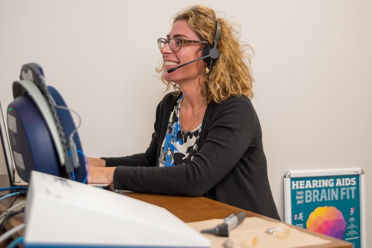 A hearing practitioner running a machine to test hearing loss