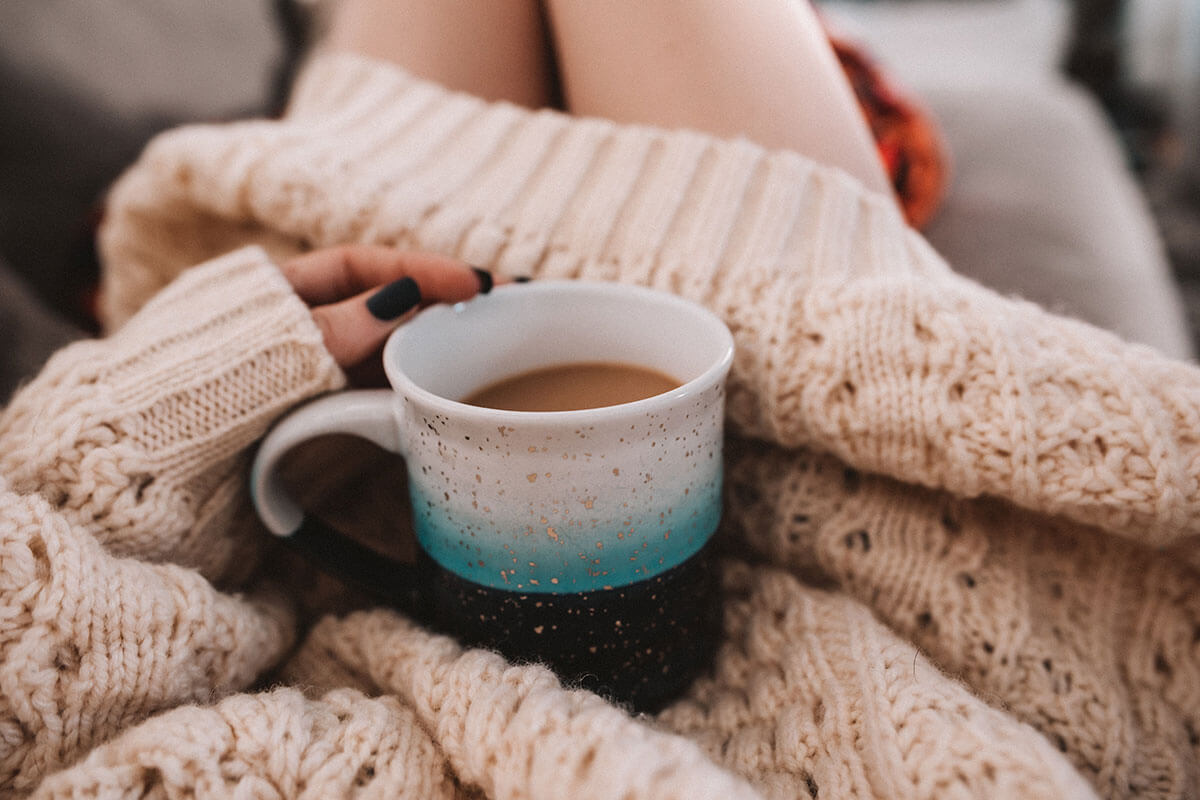 The Hygge life, part of a woman's body showing a pink sweater and a hand holding a cup of coffee