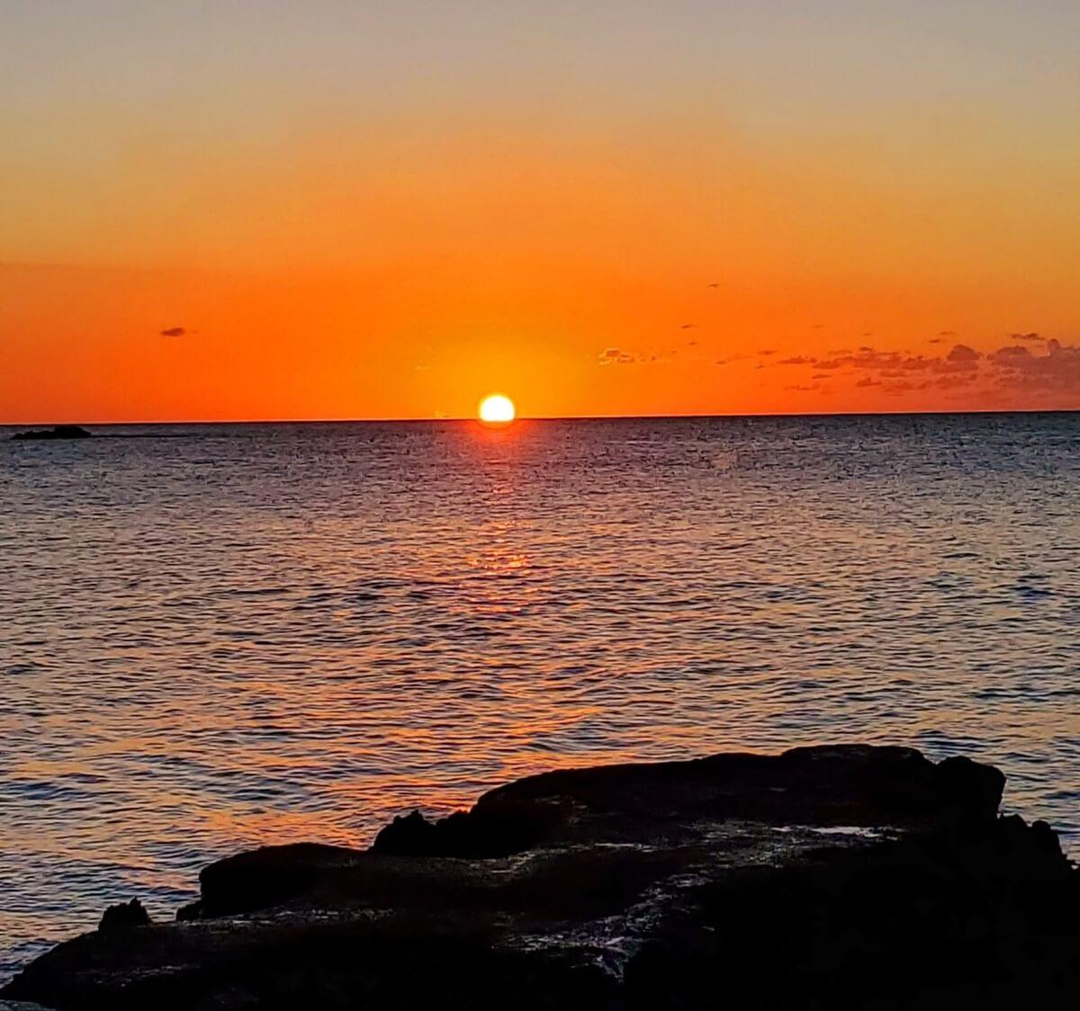 An orange Jamaican sunset over the ocean, part of Jamaica's one-love treasures