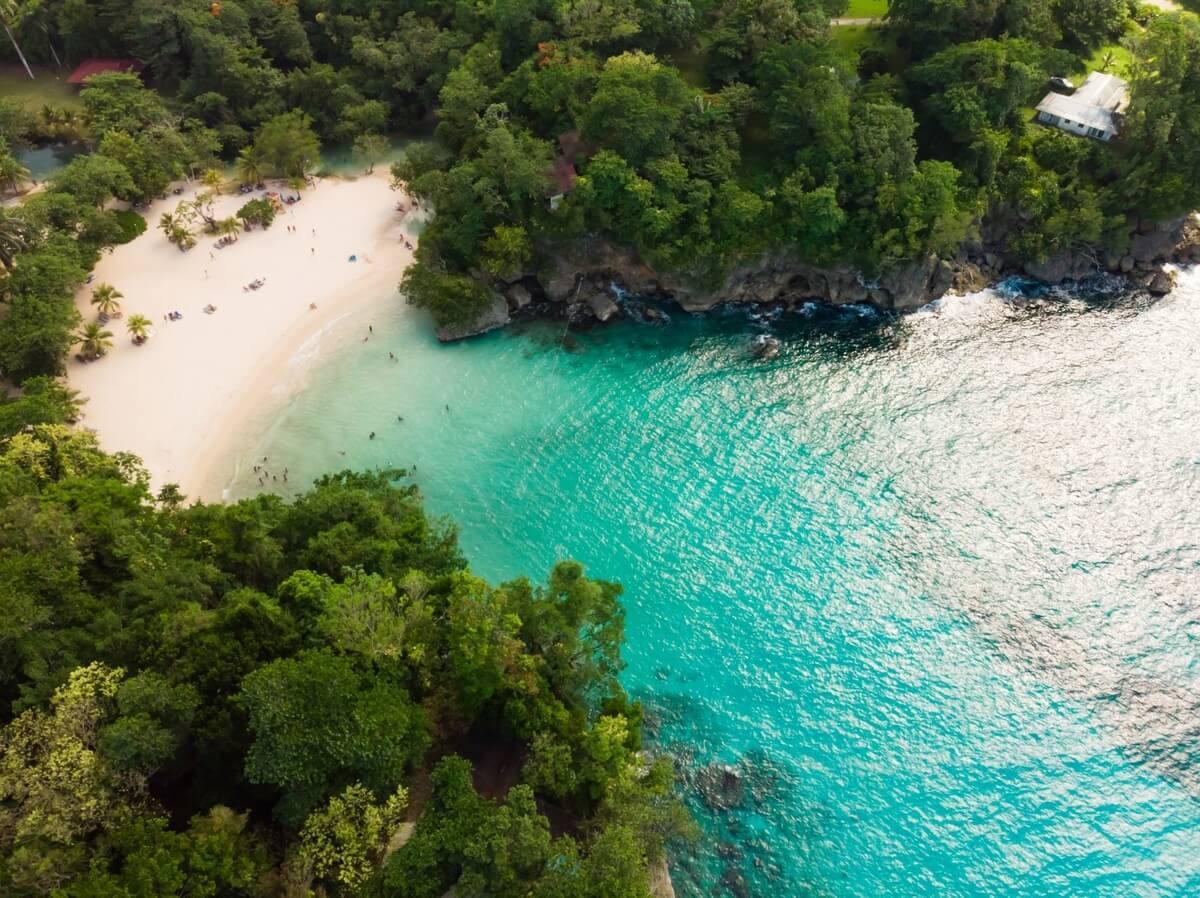 A view from above of a Jamaican beach tucked inside a treed cove with turquoise blue water, part of Jamaica's one-love treasures