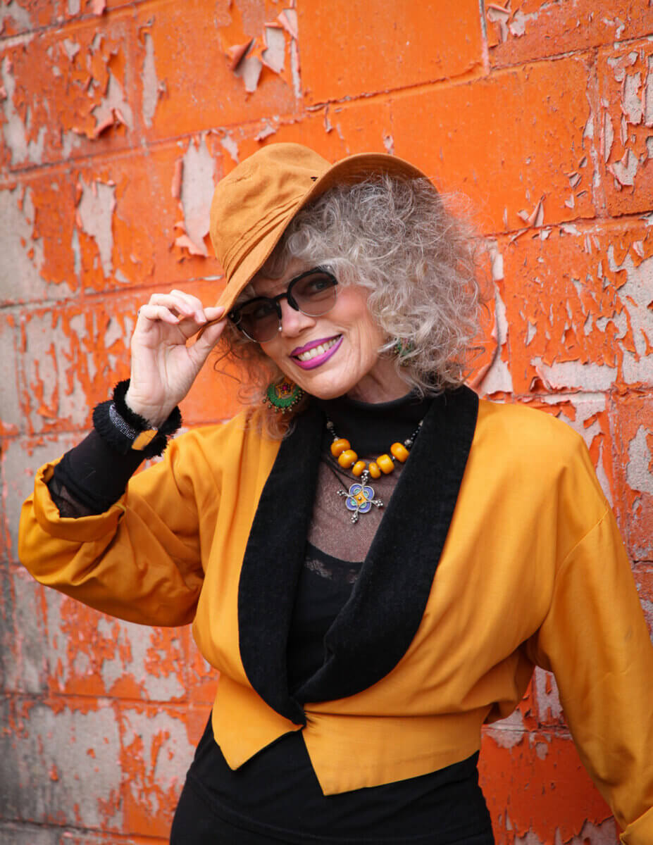 Mature woman living out loud, modelling an orange and black outfit and orange hat and sunglasses