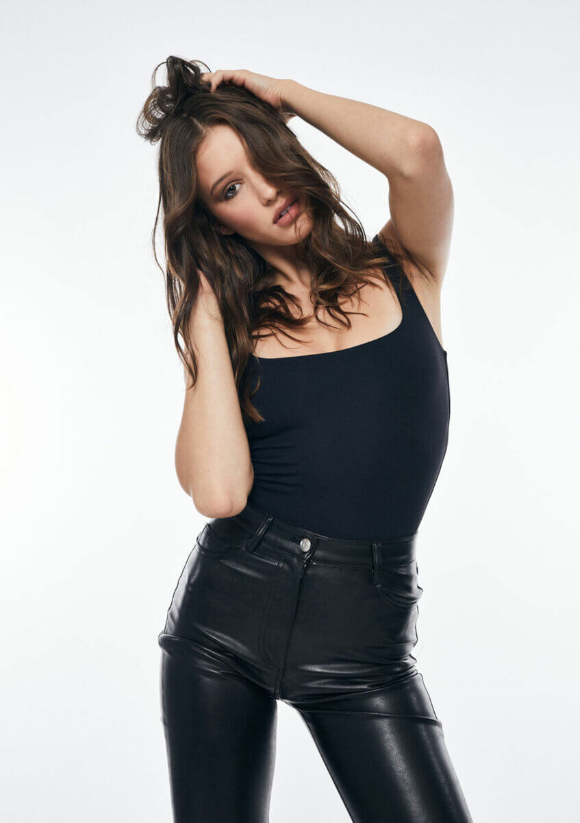 A young woman in black leather pants and tank top, one of a few monochromatic looks