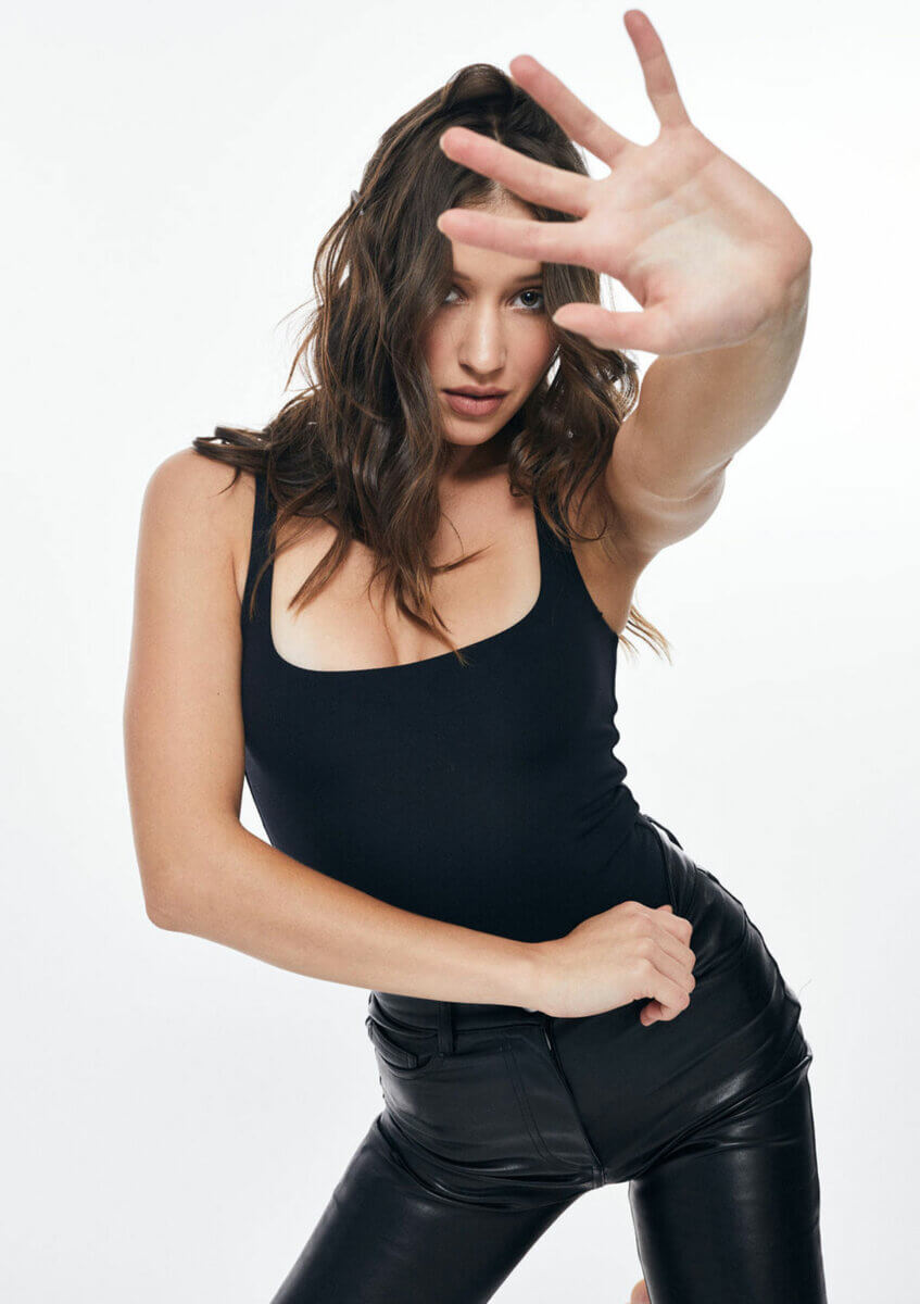 A young woman in black leather pants and black tank top holding up her hand, one of a few monochromatic looks