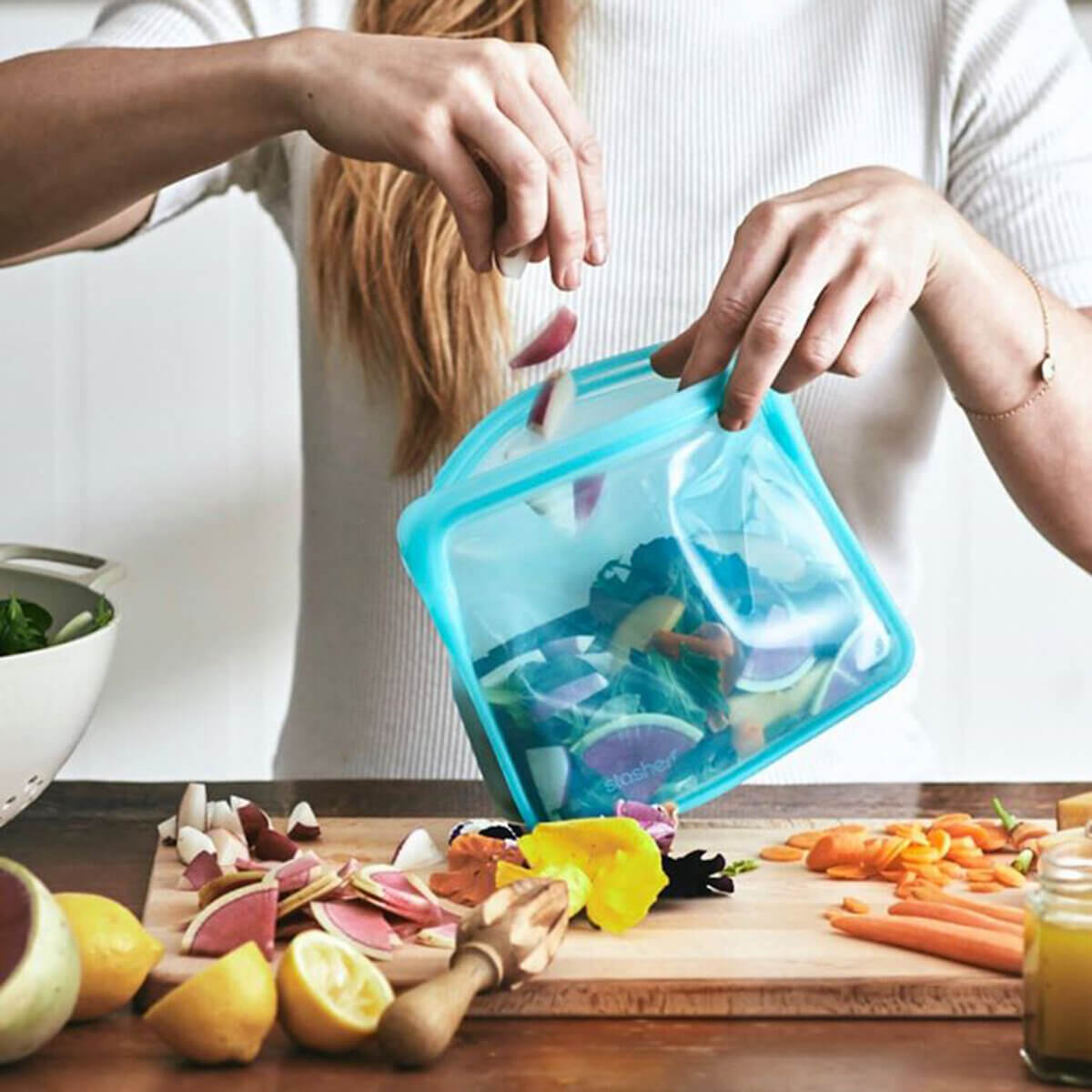 A woman holding one of the most popular plastic-free storage products - a blue Stasher bag from EarthHero, and filling it with fresh salad ingredients