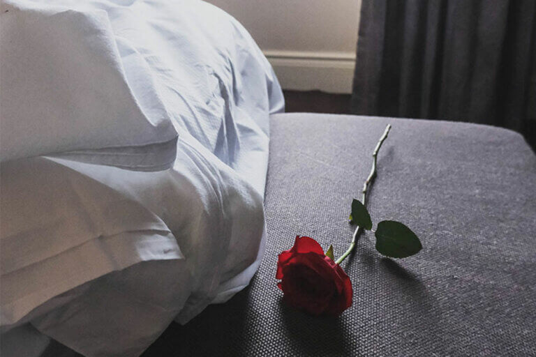 a rose laying beside a bed
