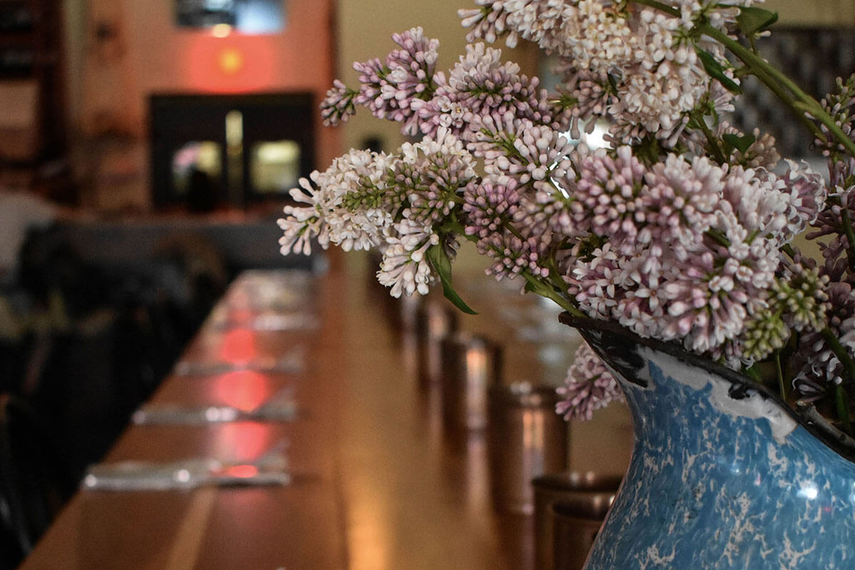 A blue vase of light purple flowers on a table set for dinner at Primal, part of the Saskatoon February City Guide
