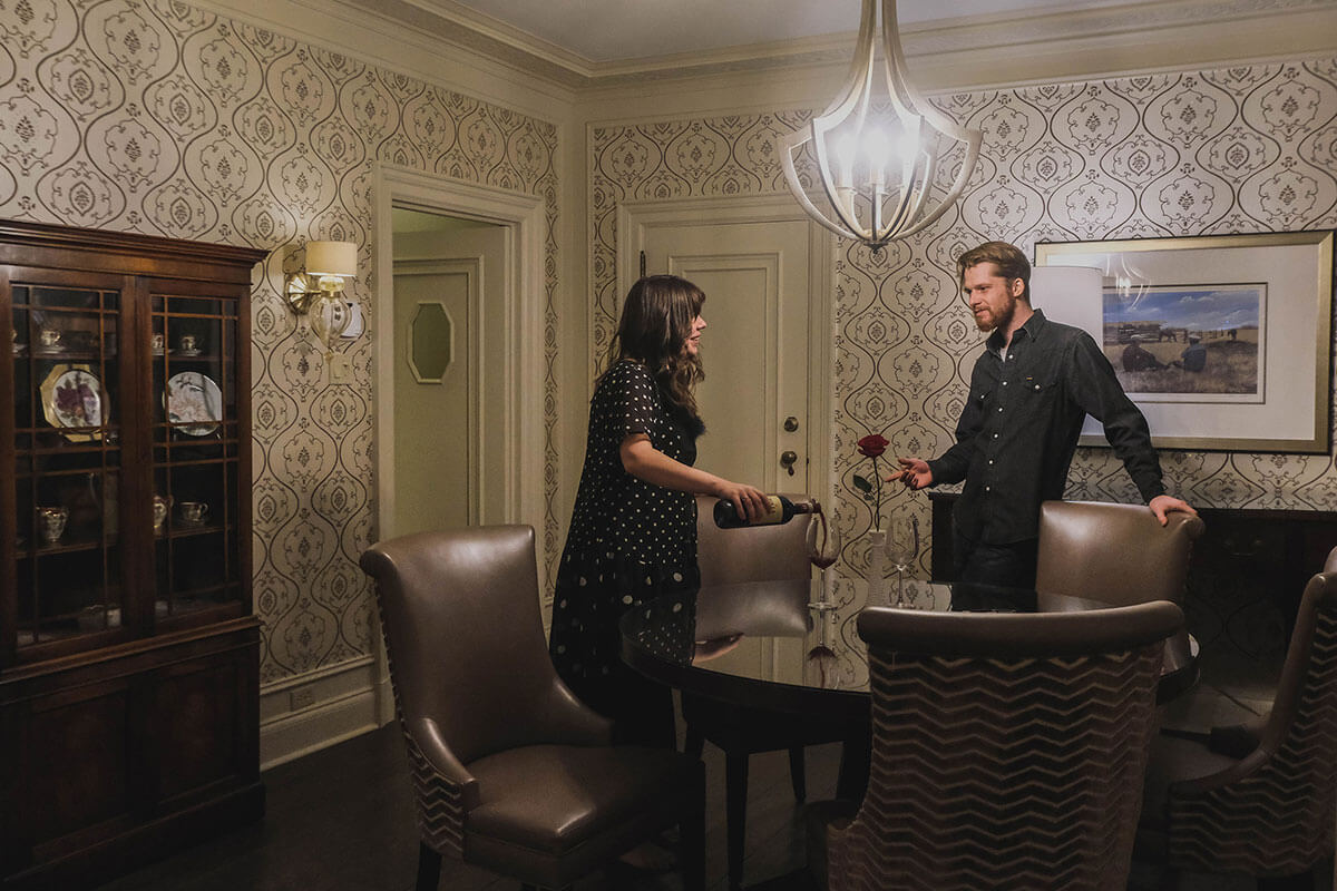 A woman and man standing at a table in their hotel room with a rose on the table