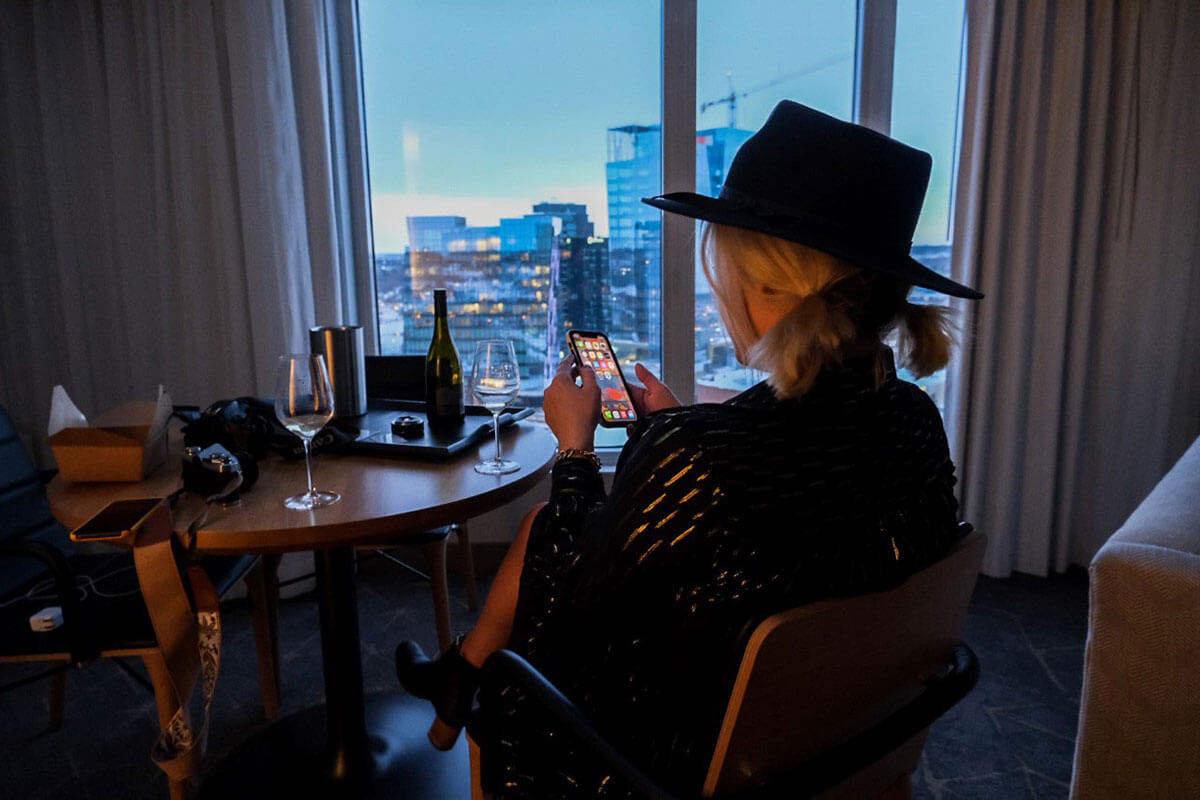A woman sitting in her hotel room with a glass of wine, looking out over the city