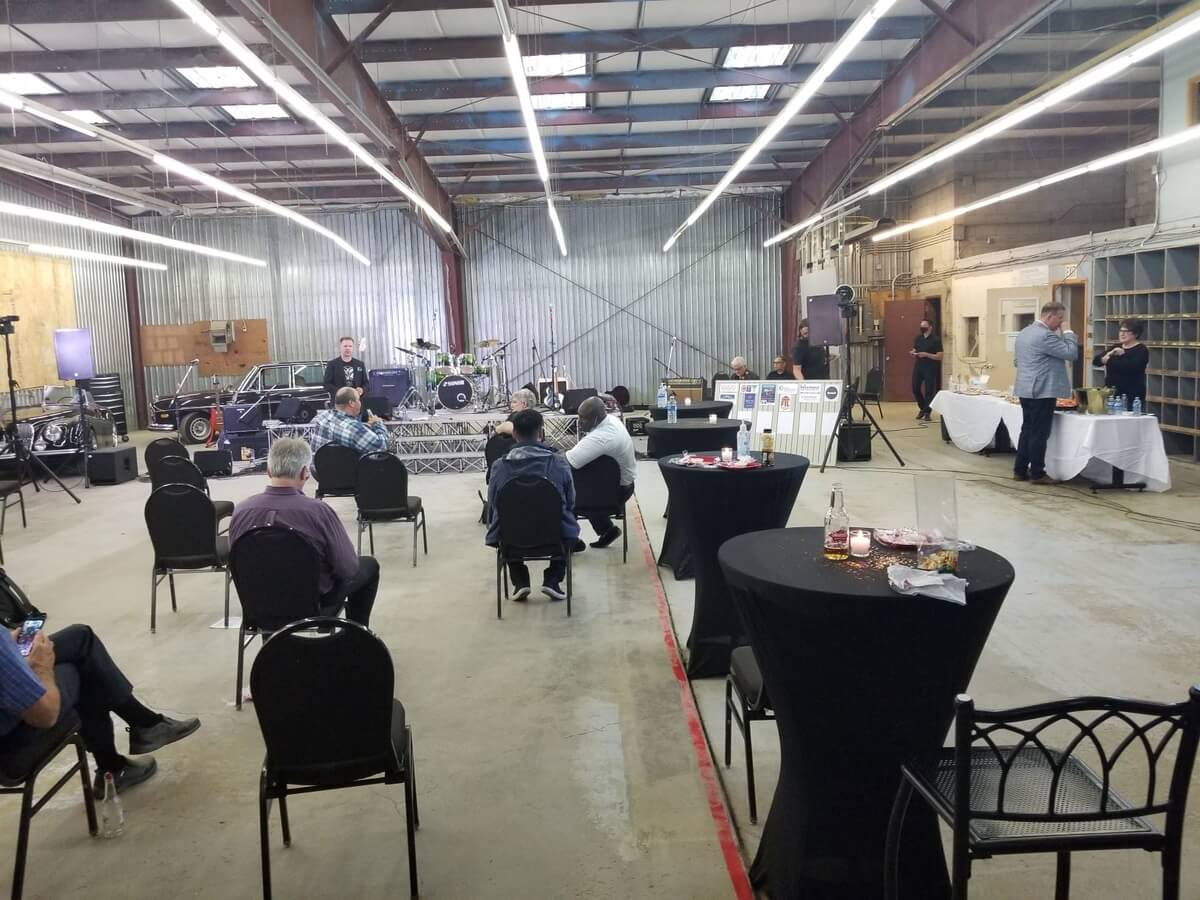 """The Garage Band and about 20 spectators in a converted bay next to  The Caring Place, taking a break at the """"point of contact"""" fundraiser"""