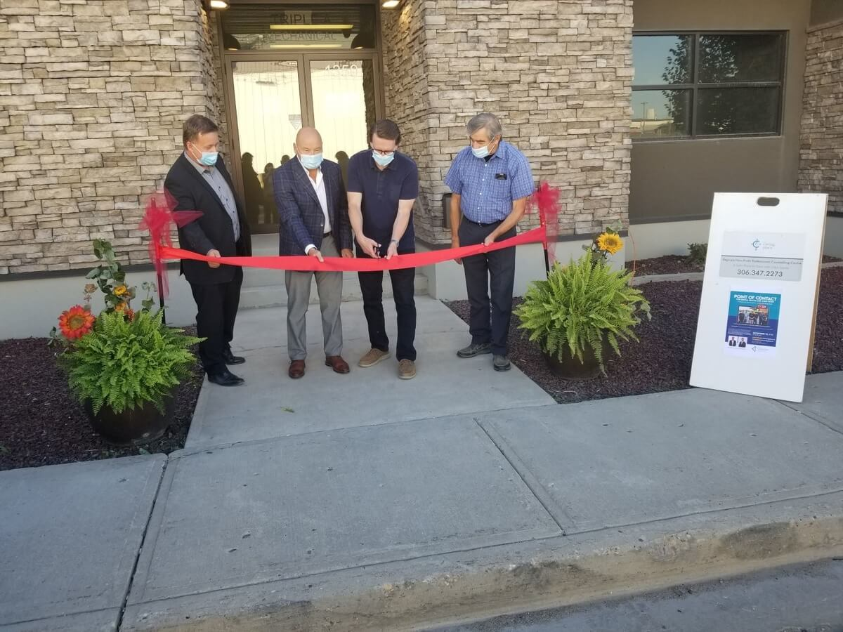 Four men hold and cut the ribbon at the official opening of The Caring Place