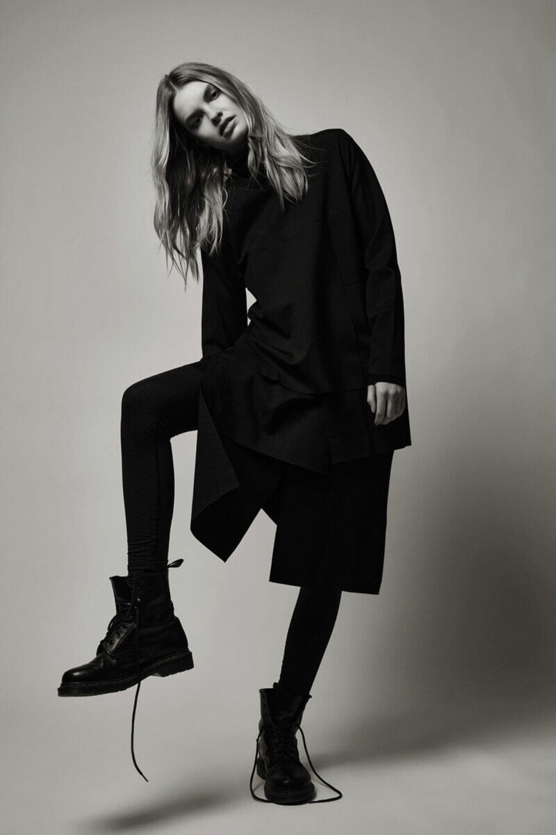 A black and white photo of a model standing in long black trench coat and combat boots