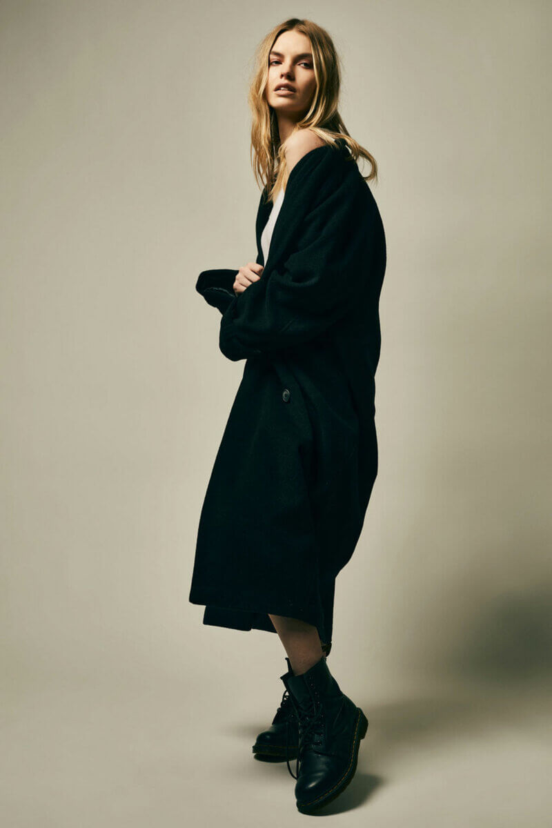 A colour photo of a model standing in long black trench coat and combat boots,