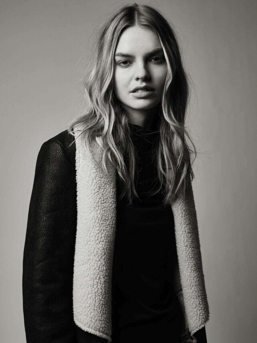 A head and shoulders black and white photo of a model standing in a black trench coat with scarf