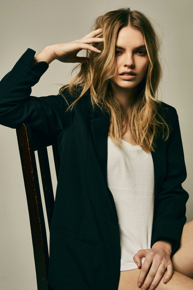 A colour photo of a seated model in a short black jacket, long white with hand on her head, in the Kate Moss factor of style