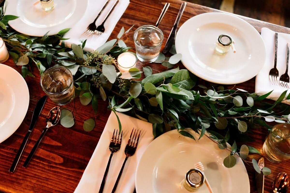 a set table with greenery, past of a sustainable COVID wedding