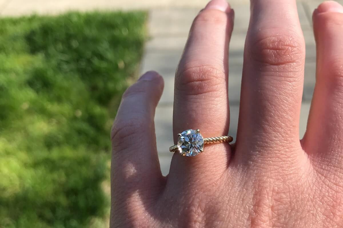 An engagement ring on a woman's left hand, planning for a sustainable COVID wedding
