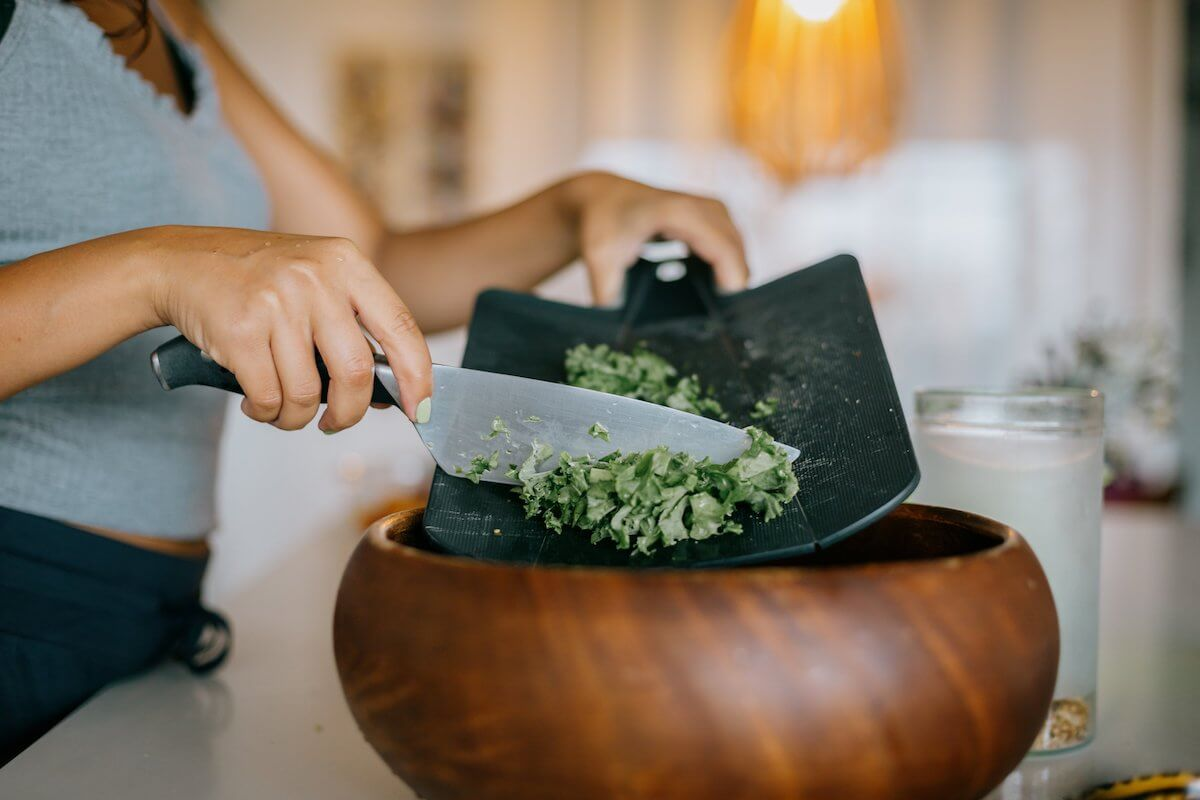 chopped kale being scraped into a wooden bowl, ingredients for air fryer