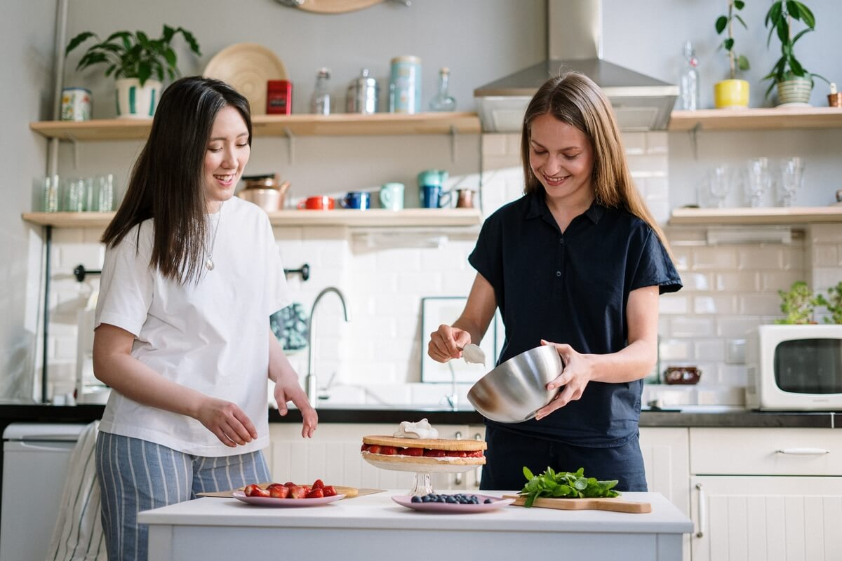 Two young women cooking a flan at a kitchen counter