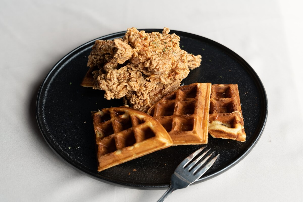 piece of fried chicken, cooked in an air fryer, and waffles on a black plate