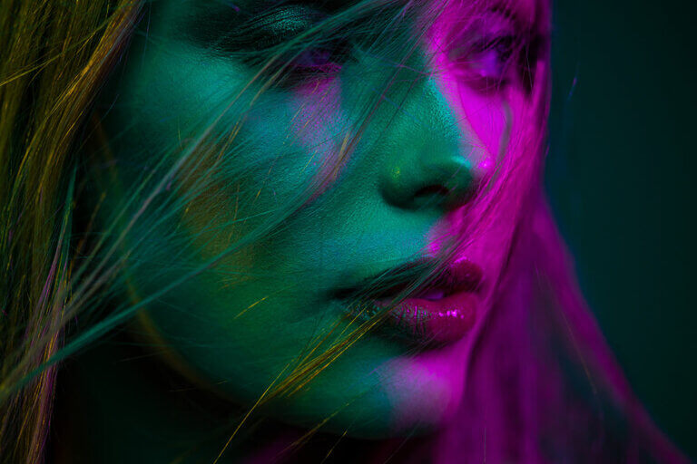 model's face with blue, green and magenta light