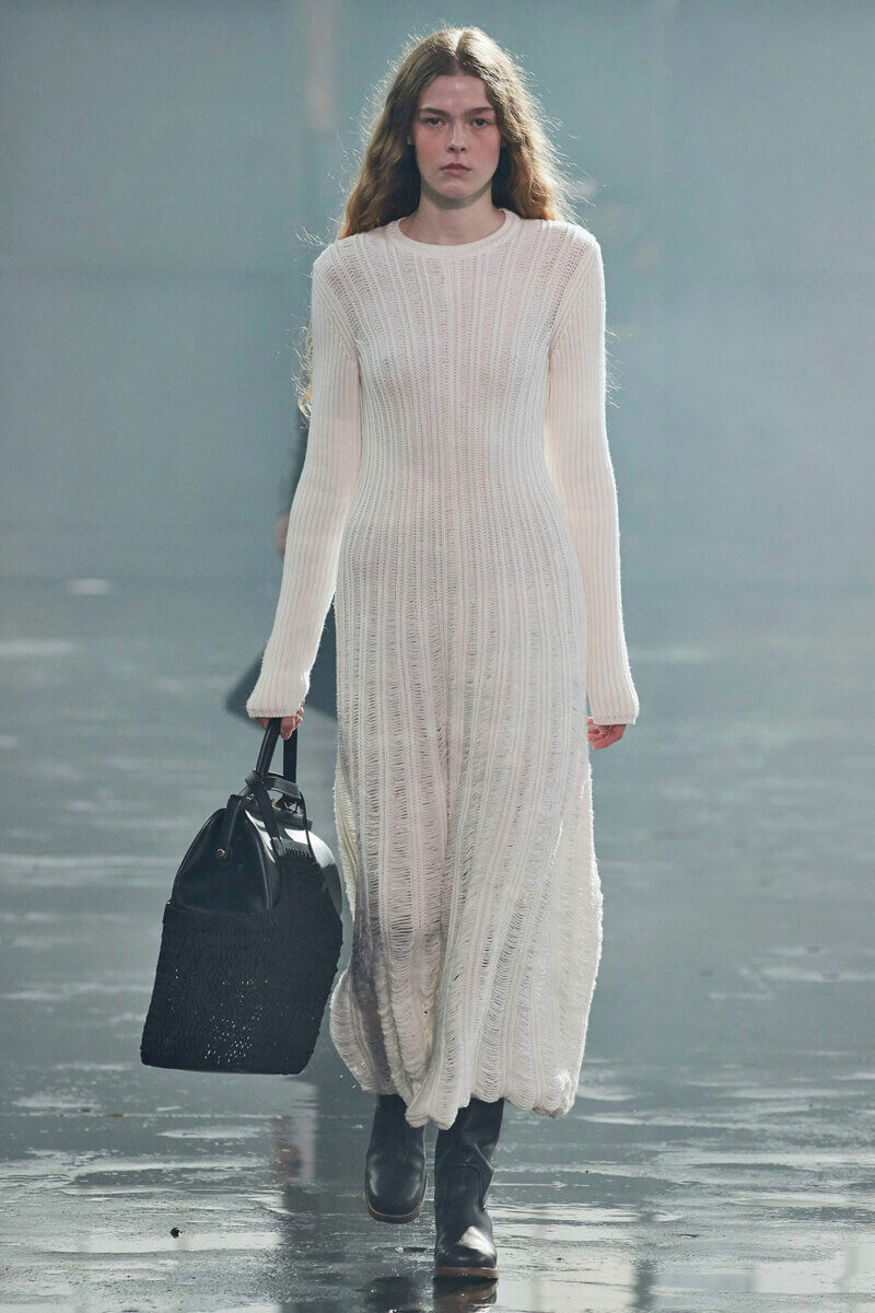 Model in long white knit dress , black combat boots and carrying black briefcase, by Gabriela Hearst RTW Fall 2021 fashion collections