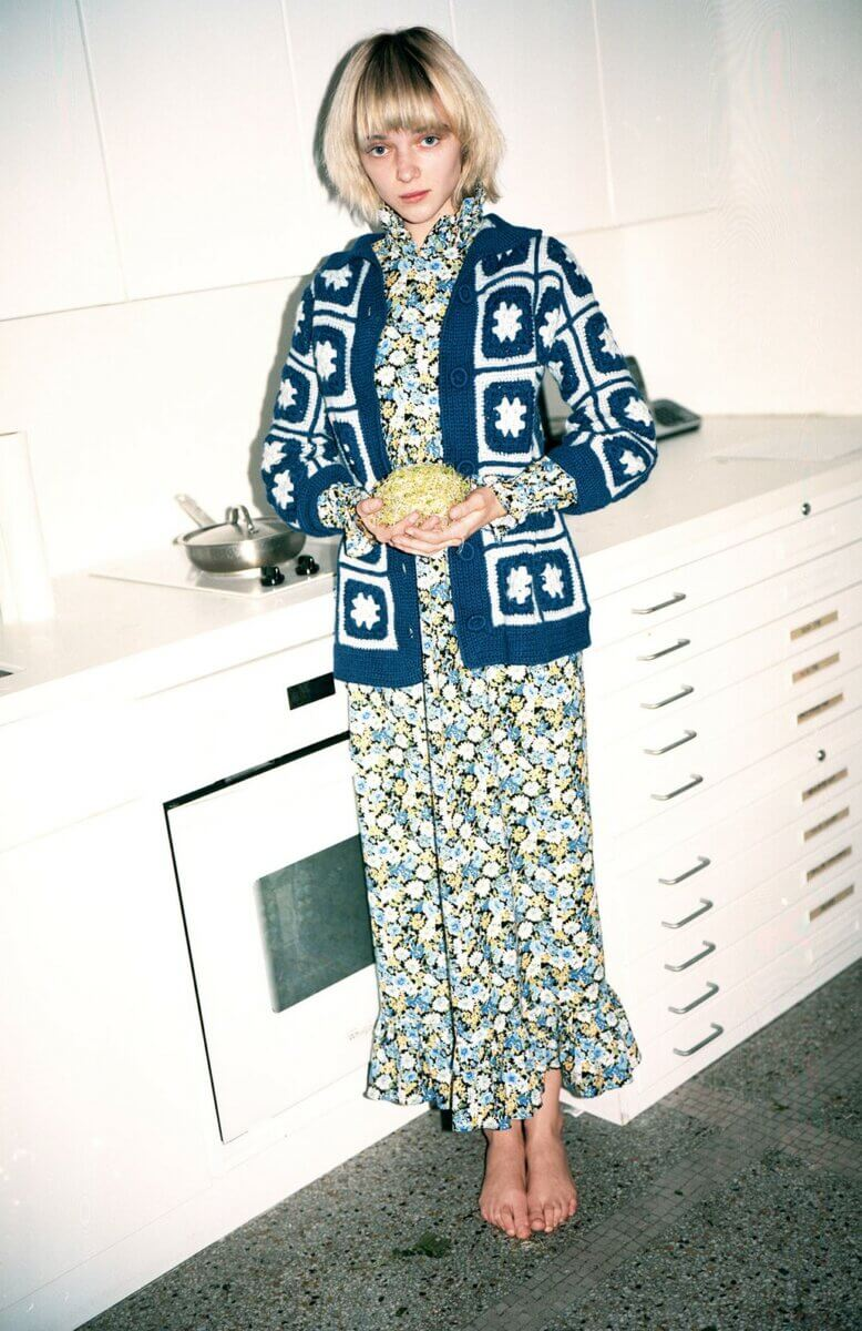 Model in a kitchen wearing a long floral dress with a blue & white knit cardigan sweater, by Batsheva RTW Fall 2021 fashion collections