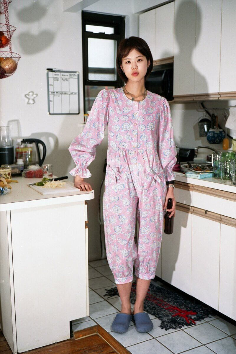 Woman in kitchen wearing pink floral pajama-style jumper, by Batsheva RTW Fall 2021 fashion collections