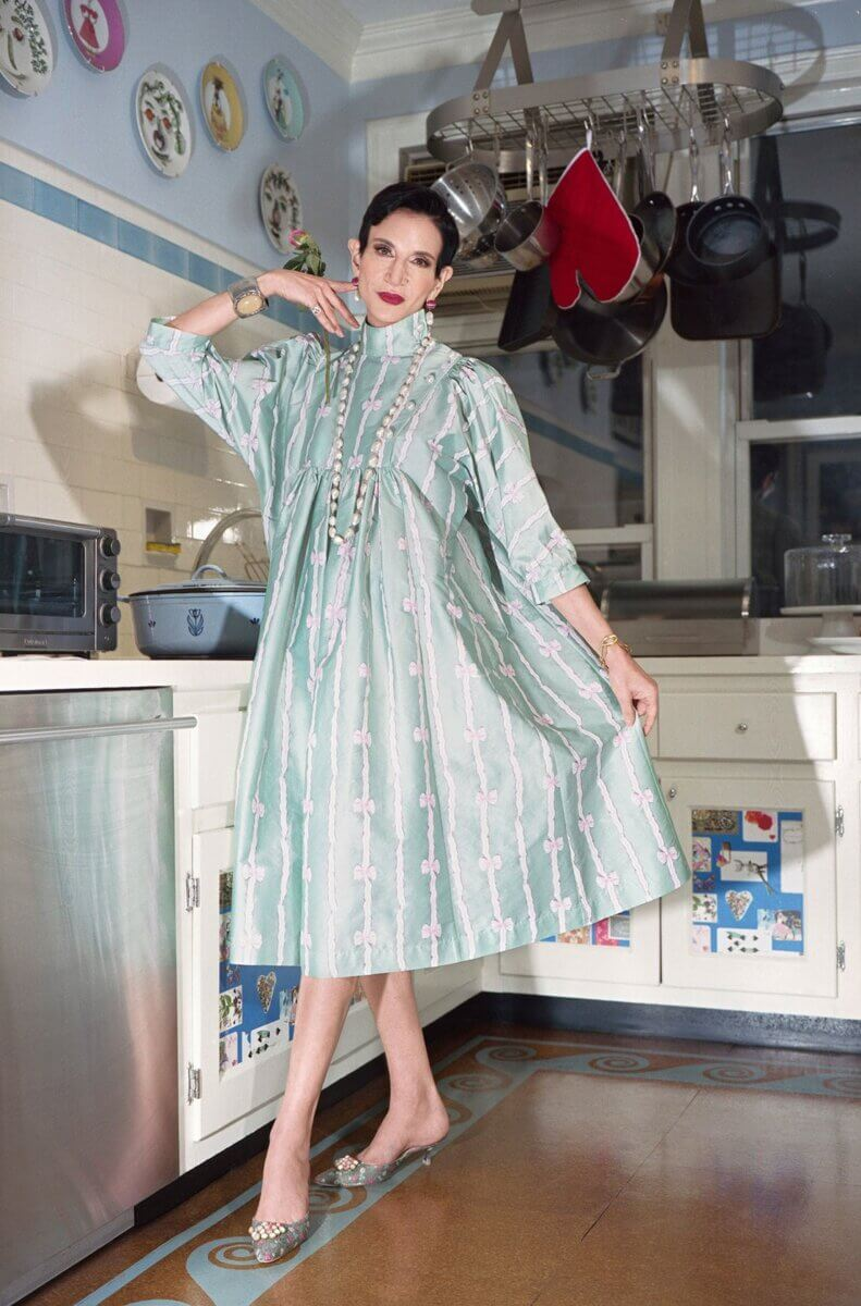 Model in a kitchen wearing a light green & pink flowing knee-length dress, by Batsheva RTW Fall 2021 fashion collections