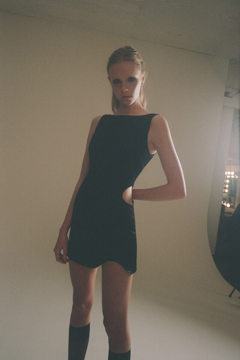 Standing model in short black dress by Sandy Liang RTW