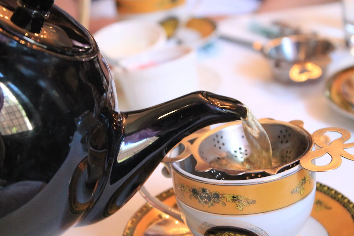tea being poured into a cup in high tea restaurants in Toronto