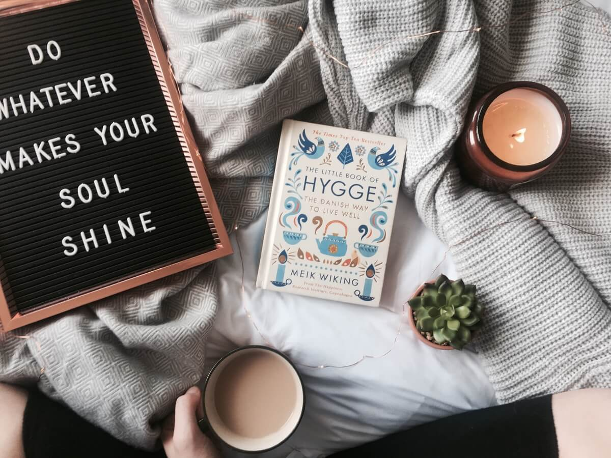 a sign, book, cup of coffee on a blanket, part of hygge healing
