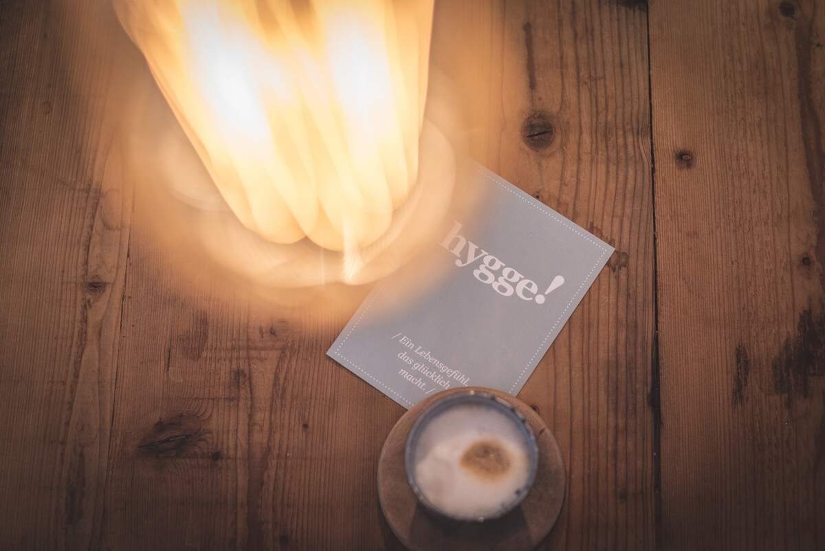 a candle, book and golden light on a wooden floor, essential for hygge healing