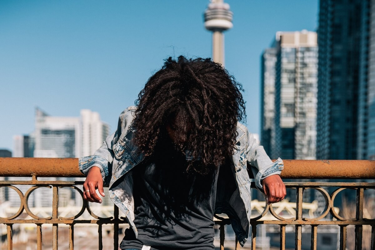 A person standing beside a bridge wearing a jean jacket and casual clothes to found at indie boutiques in Toronto